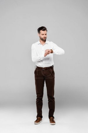 handsome businessman in white shirt looking at watch on grey
