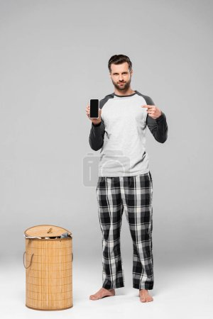 bearded man pointing with finger at smartphone with blank screen near laundry basket on grey