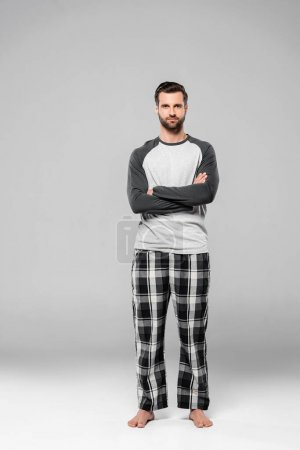 Photo for Bearded man standing with crossed arms on grey - Royalty Free Image