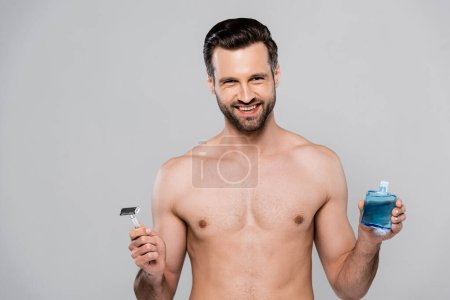 Photo for Cheerful and muscular man holding after shave lotion and razor isolated on grey - Royalty Free Image