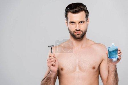 Photo pour Homme barbu et musclé tenant après le rasage lotion et rasoir isolé sur gris - image libre de droit