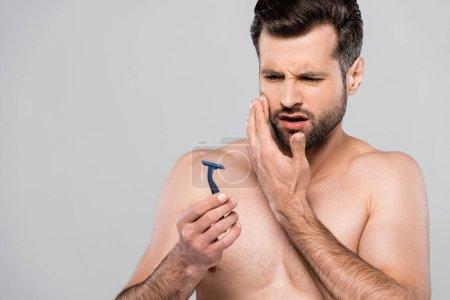 Photo pour Mécontent homme regardant rasoir isolé sur gris - image libre de droit