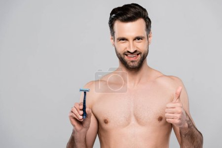 handsome man holding razor while smiling and showing thumb up isolated on grey