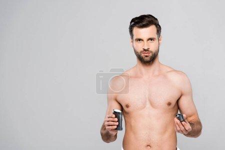 Photo pour Homme barbu et musclé tenant déodorant bâton solide isolé sur gris - image libre de droit