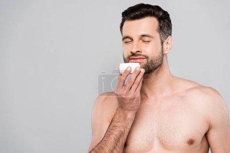 Photo pour Heureux homme barbu odeur crème cosmétique isolé sur gris - image libre de droit