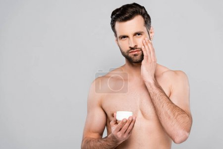 Photo for Shirtless man holding container while applying cosmetic cream isolated on grey - Royalty Free Image
