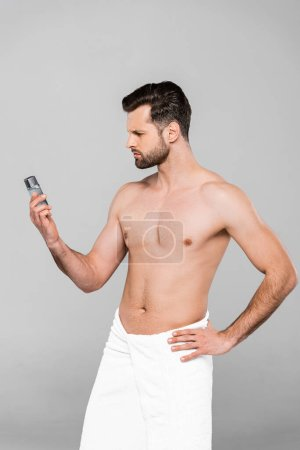 Photo pour Homme barbu et musclé en serviette regardant déodorant debout avec la main sur la hanche isolé sur gris - image libre de droit