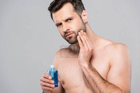 bel homme tenant bouteille avec lotion après rasage et visage touchant isolé sur gris