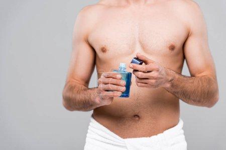 Photo pour Vue recadrée de l'homme musclé tenant bouteille avec lotion après rasage isolé sur gris - image libre de droit