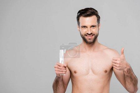 Photo pour Homme heureux et musclé tenant dentifrice et brosse à dents tout en montrant pouce vers le haut isolé sur gris - image libre de droit