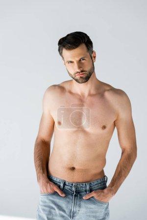 Photo pour Homme beau et torse nu debout avec les mains dans les poches sur gris - image libre de droit
