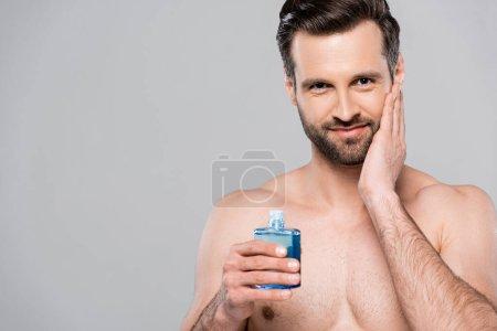 Photo pour Homme heureux tenant bouteille avec lotion bleue après rasage et toucher le visage isolé sur gris - image libre de droit