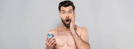 panoramic shot of surprised man touching face and holding bottle with blue after shave lotion isolated on grey