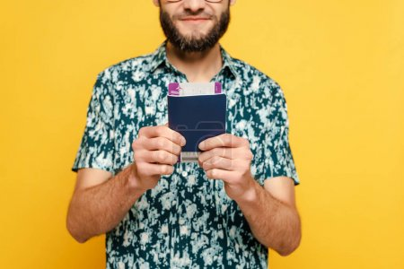 cropped view of smiling bearded guy with air ticket and passport on yellow