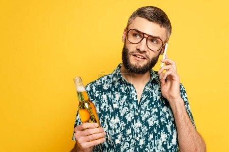 Photo pour Cher barbu gars dans des lunettes avec bouteille rafraîchissante de bière parler sur smartphone isolé sur jaune - image libre de droit