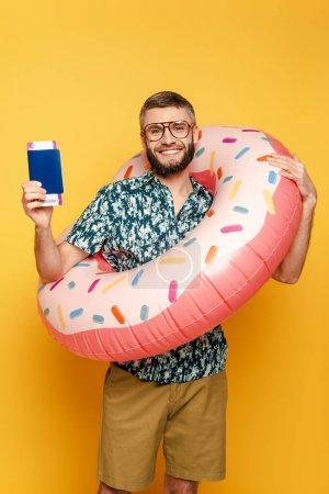 Photo pour Sourire barbu gars dans des lunettes avec anneau de natation beignet et passeport sur jaune - image libre de droit