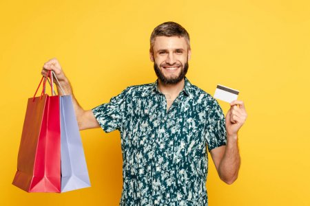 happy bearded guy with shopping bags and credit card on yellow
