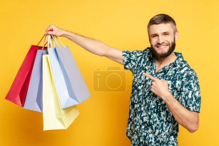 Photo for Happy bearded guy pointing at shopping bags on yellow - Royalty Free Image