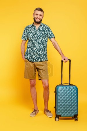full length view of happy bearded guy with travel bag on yellow