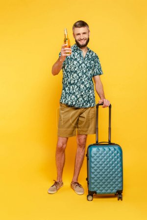 full length view of happy bearded guy with travel bag and beer on yellow