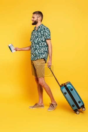 Photo for Full length view of happy bearded guy with travel bag and passport on yellow - Royalty Free Image