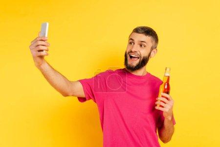 Photo pour Heureux barbu gars en rose t-shirt prendre selfie avec de la bière sur jaune - image libre de droit