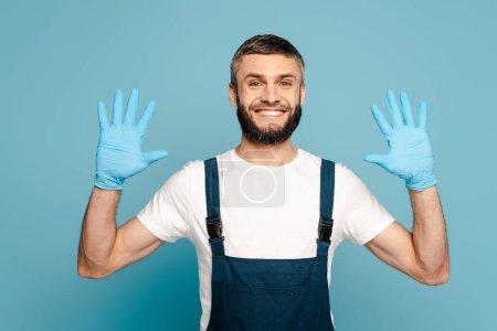 Photo pour Nettoyant heureux en uniforme montrant les mains dans des gants en caoutchouc sur fond bleu - image libre de droit