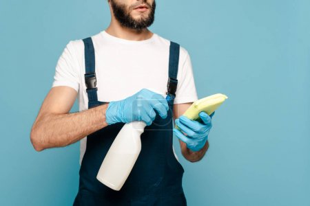 Photo for Cropped view of cleaner in uniform and rubber gloves holding detergent and sponge on blue background - Royalty Free Image