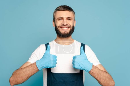 happy cleaner in uniform and rubber gloves showing thumbs up on blue background