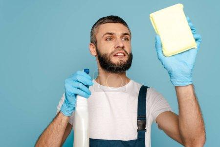 Photo pour Nettoyant en uniforme et gants en caoutchouc avec détergent et éponge sur fond bleu - image libre de droit