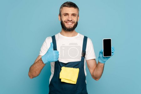 Photo for Happy cleaner in uniform and rubber gloves with rug holding smartphone and showing thumb up on blue background - Royalty Free Image