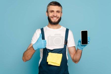 Photo pour Nettoyeur heureux en uniforme et gants en caoutchouc avec tapis tenant smartphone et montrant pouce vers le haut sur fond bleu - image libre de droit