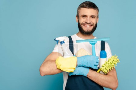 Photo for Happy cleaner in uniform and rubber gloves holding cleaning supplies on blue background - Royalty Free Image