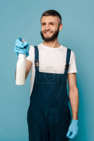Photo for Happy cleaner in uniform and rubber gloves holding spray detergent on blue background - Royalty Free Image