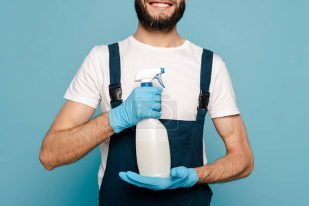 Photo for Cropped view of happy cleaner in uniform and rubber gloves holding spray detergent on blue background - Royalty Free Image