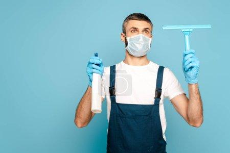 Photo pour Nettoyant dans le masque médical tenant détergent et raclette sur fond bleu - image libre de droit