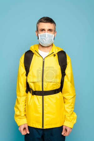 Photo for Deliveryman in medical mask and yellow uniform with backpack on blue background - Royalty Free Image