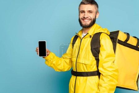 Photo pour Livreur heureux en uniforme jaune avec sac à dos montrant smartphone avec écran blanc sur fond bleu - image libre de droit