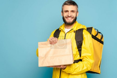 Photo for Smiling deliveryman in yellow uniform with backpack holding paper package on blue background - Royalty Free Image