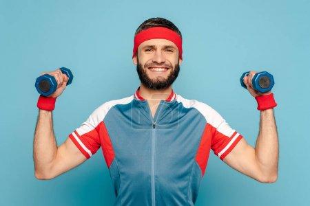 Photo for Smiling stylish sportsman exercising with dumbbells on blue background - Royalty Free Image