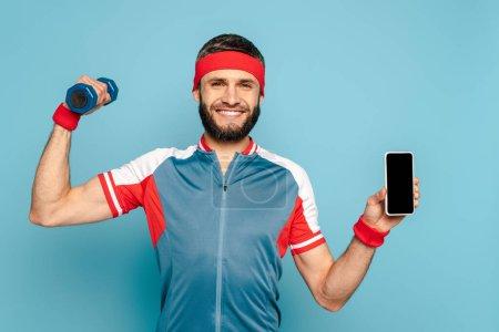 Photo pour Sportif élégant souriant faisant de l'exercice avec haltère et tenant smartphone sur fond bleu - image libre de droit