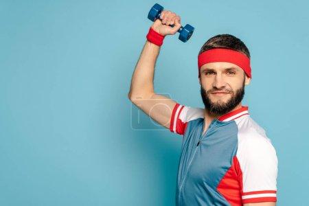 stylish sportsman exercising with dumbbell on blue background