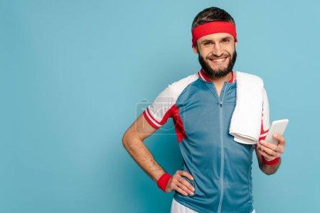 Photo pour Sportif élégant souriant avec serviette en utilisant un smartphone sur fond bleu - image libre de droit