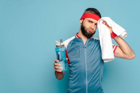 Photo for Tired stylish sportsman with towel and water on blue background - Royalty Free Image