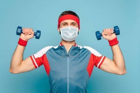 Photo pour Un sportif élégant en masque médical s'entraînant avec des haltères sur fond bleu - image libre de droit