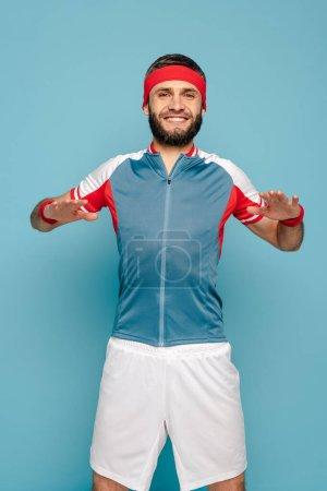 Photo pour Sportif élégant heureux faisant de l'exercice sur fond bleu - image libre de droit