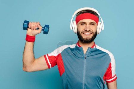 Photo pour Sportif élégant heureux dans les écouteurs exercice avec haltère sur fond bleu - image libre de droit