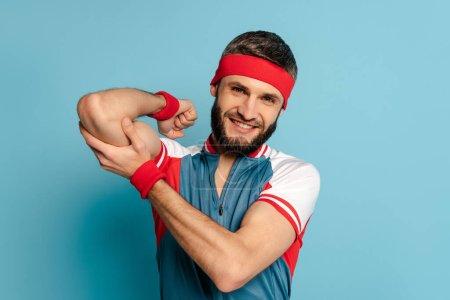Photo for Smiling stylish sportsman touching biceps on blue background - Royalty Free Image