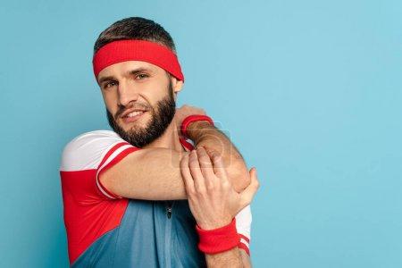 Photo pour Barbu sportif élégant échauffement bras sur fond bleu - image libre de droit