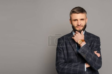 Photo for Pensive handsome bearded businessman in suit on grey background - Royalty Free Image